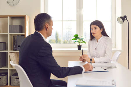Female professional human resources manager listens carefully to the man who came to get a job in the company. Woman conducts an interview with a confident male candidate for the vacancy. Banque d'images