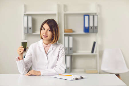Young woman nutritiologist holding glass of green chlorophyll spirulina drink, showing its benefits for health online during teleconference with patient. Healthy lifestyle, clean eating, weight loss