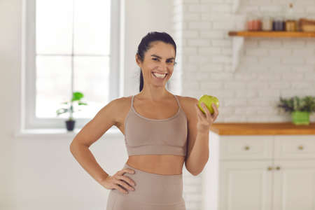 An apple a day keeps the doctor away. Happy smiling fit woman standing in the kitchen, holding fresh green Granny Smith apple and looking at camera. Healthy eating habits, dieting, weight loss concept