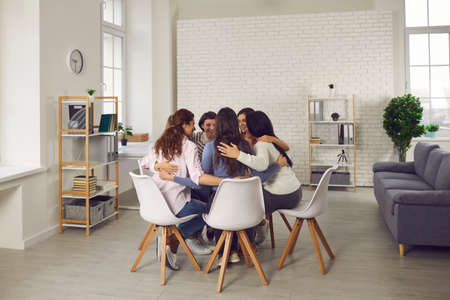 Happy women sitting close in circle in company office, huddling and talking. Female patients in group therapy meeting supporting each other. Business team members motivating each other for success Imagens