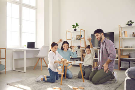 Family weekend entertainment. Mom, dad, daughter and son play game sitting at a table from which a wooden tower falls. Fun board games for family leisure. Stay at home activity for kids.