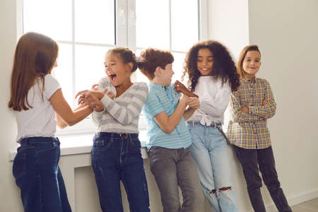 Group of happy diverse friends playing, tickling each other, laughing, having fun during school recess or party at home. Childrens social interaction with peers, intercultural kids community concepts
