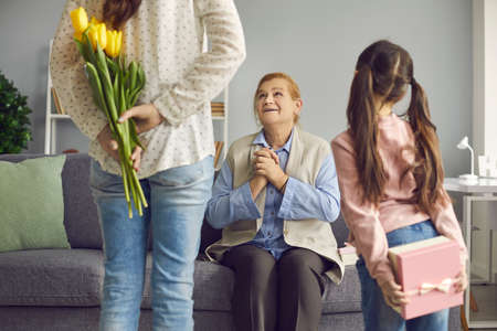 Joyful senior woman receives congratulations on Womens Day from her daughter and granddaughter. Woman and a child turn their backs to the camera and hold flowers and a gift. Selective focus.