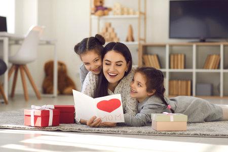 母亲节。双胞胎姐妹拥抱并通过给她的手工卡和礼物迎接他们的母亲。说谎在与孩子的地板上的兴奋的愉快的母亲和读问候。家庭和爱的概念。