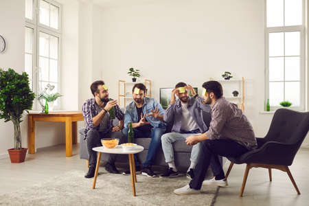 Mens leisure. Group of male friends sit on a sofa in the living room with stickers on their foreheads and play the game Who am I. Friends have fun at home playing games and drinking beer with chips.
