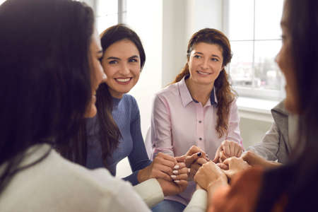 Happy smiling young women sitting in circle and holding hands in corporate meeting or group session with motivational coach. Concept of female community, support and achieving goals together. Close-up