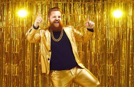 Rich chubby man in a golden suit dances at a party or disco on a bright shiny background. Cheerful unrestrained red-haired man with a massive chain around his neck and dances and sings songs.
