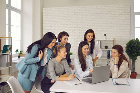 Happy female business team working on business project together. Group of positive smiling young women meeting in office, using laptop computer, talking, sharing ideas and discussing company strategy Imagens