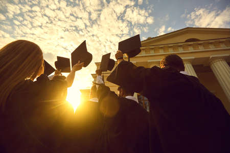 Group of young people university graduates in traditional masters mantles standing and holding diplomas in raised hands over sunset and university building background, bottom rear view