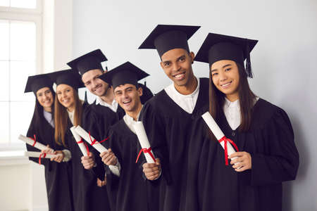 Smiling international students in traditional academic caps and gowns celebrating graduation. Group portrait of happy multiethnic college or university graduates holding diplomas and looking at camera Standard-Bild
