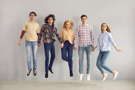 Full length group portrait of cheerful jumping young people. Full body studio shot of happy school students, college mates, or university friends in casual wear leaping for joy and having fun together
