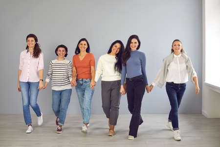 Group of happy confident young women in their 20s and 30s smiling and looking at camera while walking together hand in hand ready to support each other. Concept of power, success and female solidarity