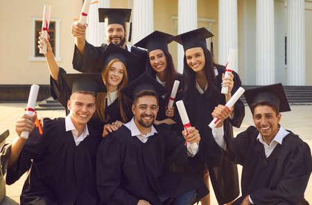 以大学大楼为背景,男女学生微笑着庆祝毕业的集体照片。成功大学毕业理念