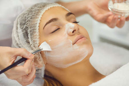 Professional cosmetologist applies white cosmetic cream to a girl lying on a massage table in a modern spa. Woman uses a special brush to work. Close up.