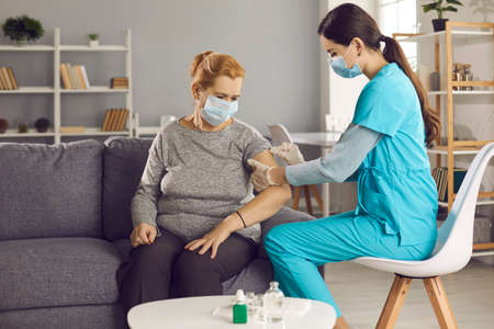 Safe vaccination for old people. Mature woman in medical face mask getting flu or Covid-19 vaccine sitting on sofa at home. Doctor or nurse giving flu or Covid-19 shot to senior female patient Banque d'images