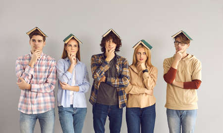 These people seem to be up to something. Students stand on a gray background with a pensive expression having books on their heads. Funny girls and guys ponder their ideas, plans or lecture topics.