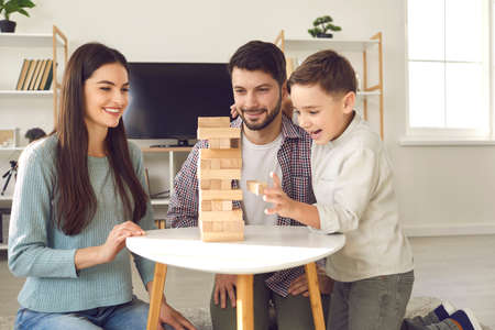 Happy family with child taking blocks from tumble tower. Smiling young Caucasian couple with little son enjoying free time on weekend at home, having fun and playing exciting board game together