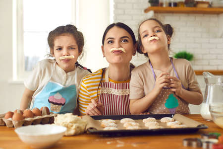 Happy family having fun while cooking. Children and mother baking cookies in the kitchen together. Cheerful young mom and little daughters playing with dough and making funny faces with fake mustaches