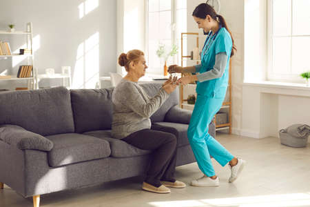 Support and care. Young doctor visiting senior female patient at home. Friendly nurse at clinic, hospital or assisted living facility helping senior woman take medicine and giving her glass of water