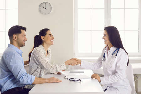 Happy woman patient giving gratitude handshake to doctor get good news about pregnancy on appointment at clinic office. Satisfied caucasian family couple visit physician for healthcare consultation Foto de archivo