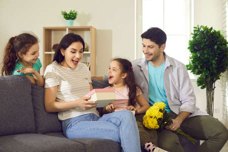 Happy family celebrating Mothers or Womens Day at home. Children and father wishing mom love, joy and happiness. Young woman enjoys flowers and birthday gifts from her husband and little kids