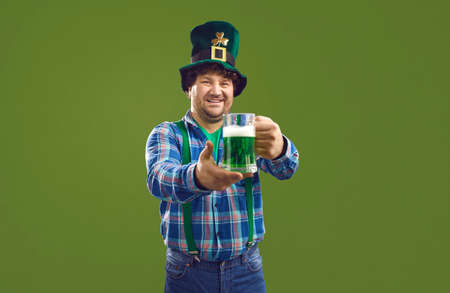 Patricks day Ireland traditional party celebration. Smiling caucasian bearded man in Leprechaun top hat holding glass offering beer or Irish ale pint isolated on green copy space background