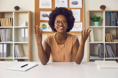 Successful project completion, deadline fulfillment, working day end. Portrait relieved attractive young african american woman in eyeglasses looking up with raised palms sitting at office desk