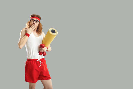 Man in sportswear covers mouth with hand surprised by amazing sports equipment sale. Funny athlete standing on gray free space background, holding gym mat and fitness dumbbells and looking at camera