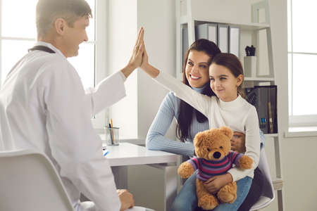 Happy little girl patient gives five smiling male pediatrician after medical examination. Child with a favorite toy sits in his mothers arms during a visit to the office of a medical clinic. 스톡 콘텐츠