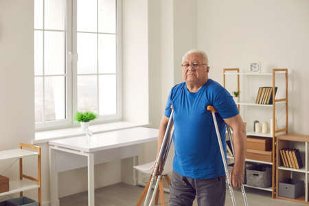 Domestic life of injured and disabled people. Senior person undergoes rehabilitation after injury in car accident. Weak mature man with broken leg or physical disability walking with crutches at home