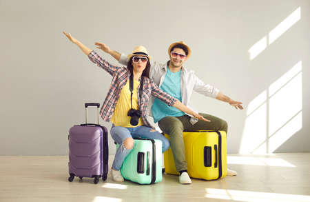 Portrait of attractive young cheerful couple travelers humorous gesture flying like plane showing sitting on luggage bag. Summer vacation, booking flight ticket, reservation tour to touristic resort