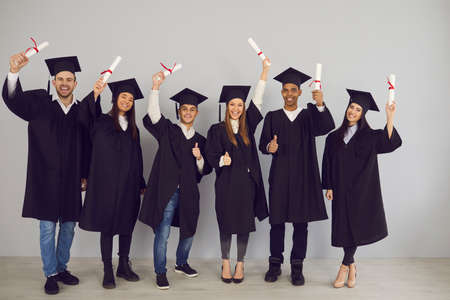 Group of cheerful multiethnic university graduates mixed race classmates standing with diplomas in raised hands, celebrating in university classroom. Successful graduation from university, education