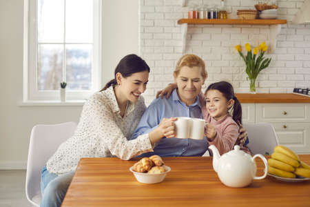 Three generations. Happy senior woman drinking tea with daughter and granddaughter sitting at home in the kitchen. Mother, child and grandmother are having fun together and jokingly clinking cups. 스톡 콘텐츠