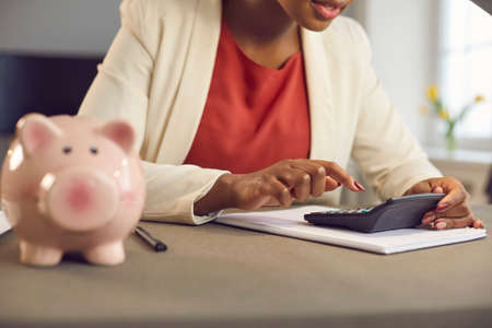 Woman at desk with moneybox and calculator counting money, planning personal household budget and calculating expenses or business income tax. People and finance, profit and loss management concept