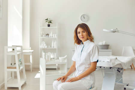 Woman cosmetologist or dermatologist looking at camera in beauty spa salon room