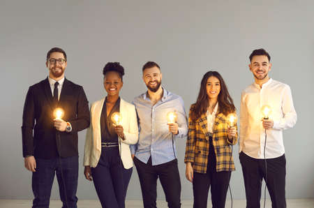 Teamwork and brainstorming, innovation idea creation and share. Diverse interracial business team positive smiling holding glowing light idea bulb standing over grey copy space studio background 스톡 콘텐츠