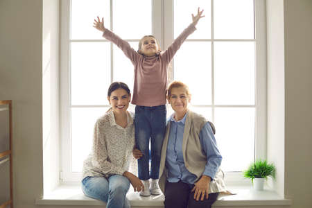 Family portrait of an older woman with her adult daughter and little granddaughter posing while sitting on the windowsill. Concept of family ties and relationships between different generations.
