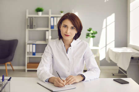 Female doctor writes notes during a video conference or listening to medical online training. Concept of online training for doctors to gain new skills, professionalism and modern technology.