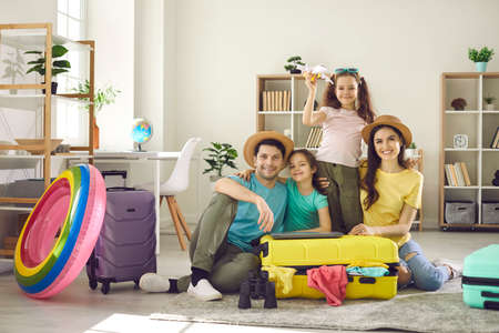 Portrait of happy family with children ready for summer vacation travel sitting on home living-room floor surrounded with packed clothes in travel suitcase bag. Holiday journey preparation 스톡 콘텐츠