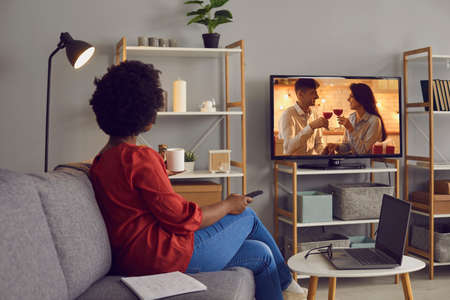 Woman enjoying good romcom serial in the evening. Single African American lady sitting alone at home, drinking coffee and watching romantic love story on soap opera entertainment TV channel, back view 스톡 콘텐츠