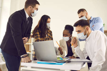 Diverse business team in face masks reduce COVID-19 infection risk. Multiethnic colleagues using laptop brainstorming idea discussing financial strategy sitting at desk. New normal office lifestyle