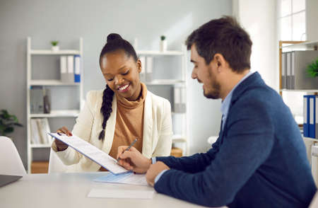 Partnership deal or vacant candidate hiring concept. Afro american businesswoman holding clipboard, caucasian businessman signing paper contract partner deal or employment agreement. Business meeting
