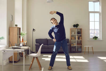Happy middle aged man doing fitness exercise during working day at office workplace. Energetic remote or freelance worker enjoying warm up stretching at home. Wellness and caring about health concept
