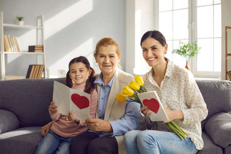 Family portrait of an older woman, her daughter and granddaughter sitting on a sofa and exchanging gifts in honor of Mothers Day. Family holds tulips, handmade cards and looks into the camera.