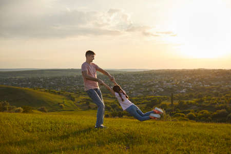 Happy fathers day. Young father playing game with his daughter in countryside at sunset, copy space.