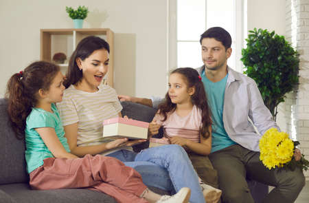 Amazed woman getting congratulations and presents from kids. Loving husband, kid prepare for mum wife gift at birthday or mother day holiday. Happy family sitting on couch in cozy home living room 스톡 콘텐츠