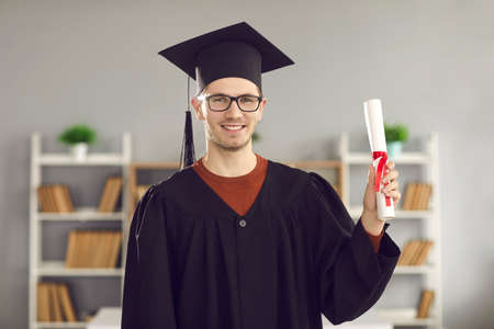 Portrait of male student in university graduate uniform showing diploma in his hands. Young guy with glasses posing in the classroom on a blurred background. Concept of education and success. 스톡 콘텐츠