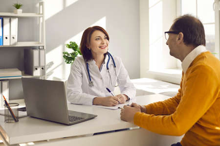 Friendly smiling caucasian woman doctor listening senior adult man complaints making notes in patient card clipboard or healthcare insurance form at initial medical consultation appointment