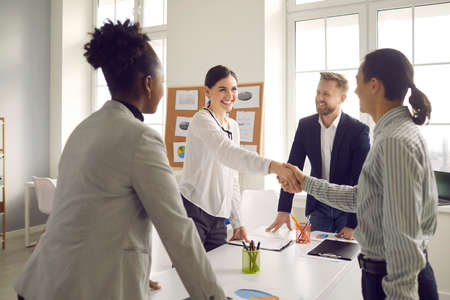 Business handshake. Happy young people greeting each other in group meeting. Smiling manager shaking hands with client after successful negotiation at the company office Standard-Bild