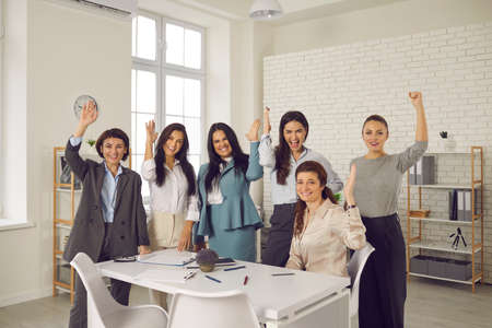 Group of happy smiling young women raising hands in corporate team meeting in office, voting for good business idea, supporting suggestion to make changes and demonstrating can-do attitude at work